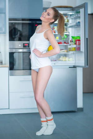 woman panties: Playful young woman posing in front of her open fridge in the kitchen in her sleepwear showing off her slender figure