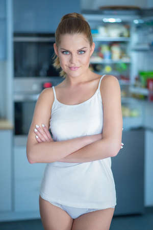 woman panties: Shapely attractive young woman in sleepwear standing smiling at the camera in a kitchen with folded arms