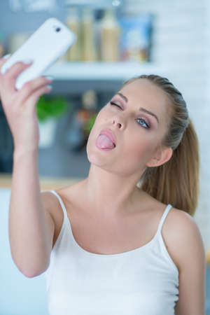 Young woman taking a selfie on her mobile playfully sticking out her tongue as she poses for the camera photo