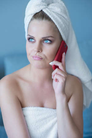 unimpressed: Thinking Woman Wearing Bath Towel Talking on Red Cell Phone Looking Unimpressed