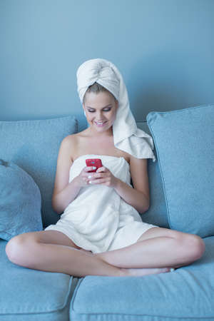 Young Woman Wearing Bath Towel Looking Down at Red Cell Phone and Sitting on Blue Sofa photo