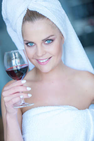 Portrait of Smiling Young Woman in White Bath Towel Holding Glass of Red Wine photo