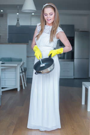 Woman Wearing White Wedding Gown and Rubber Gloves Washing Pan in Kitchen photo