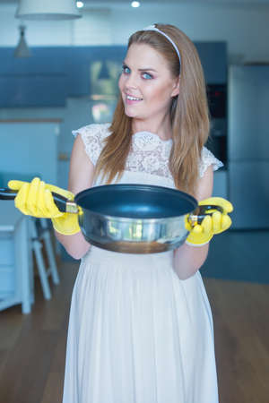 housewife gloves: Smiling Woman Wearing Wedding Gown and Rubber Gloves Holding Pan in Kitchen Stock Photo