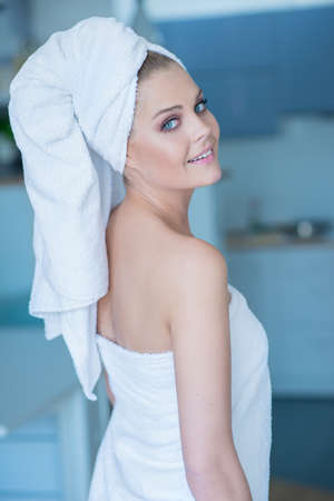 looking over shoulder: Sexy Young Woman in Bath Towel Looking Over Shoulder at Camera  Waist Up