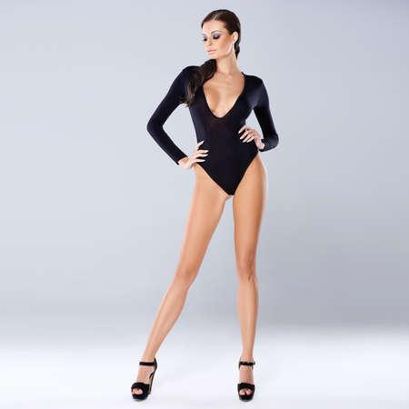 hands on hips: Sexy brunette posing isolated on gray, full body standing shot