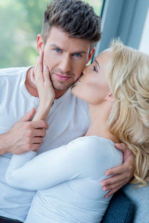 Close up Sweet Young Caucasian Couple in White. Pretty Partner Kissing Handsome Lover. photo