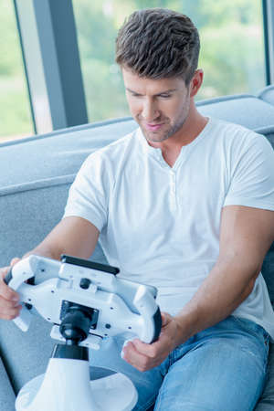 cool gadget: Middle Age Caucasian Man in White Shirt and Faded Blue Pants Playing His Cool Gadget at Home. Stock Photo