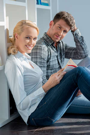 20 24: Middle Age Couple Sitting on Floor Looking at Cam Stock Photo