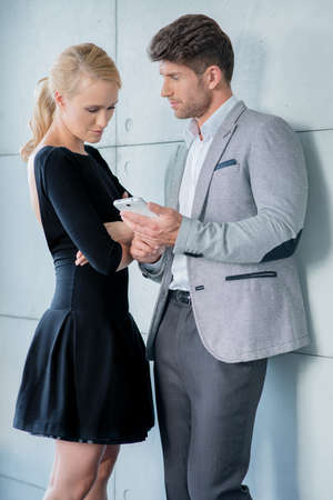 20 24: Couple in Trendy Attire Talking Something at Phone