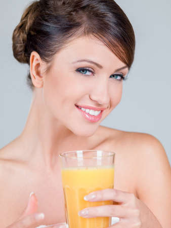 tied hair: Smiling Woman Holding Glass of Orange Juice Stock Photo