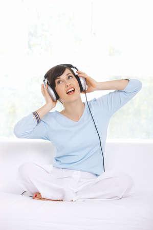 Sitting Woman Wearing Headphones and Singing photo