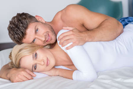 young lovers: Sweet Young Lovers Lying on Bed Looking at Cam Stock Photo