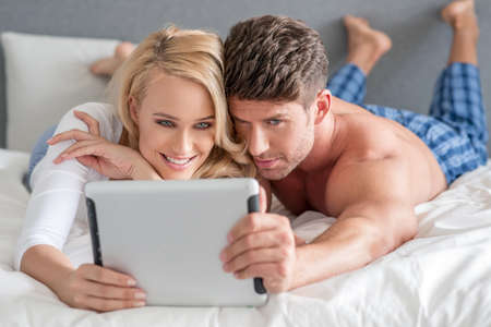20 24: Young couple reading a tablet in bed
