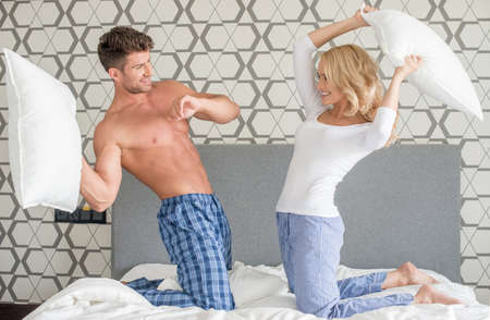 couple fight: Playful couple having a pillow fight