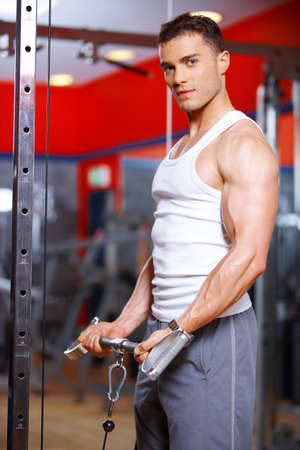 weight machine: Athletic young man working out in a gym