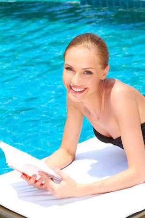 sunbed: Young woman relaxing alongside a swimming pool