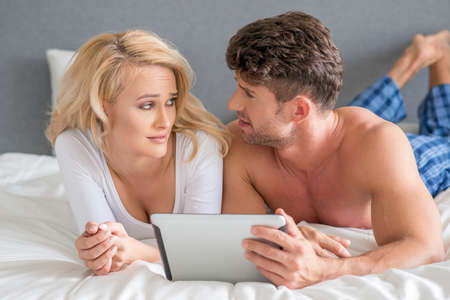 20 24: Couple Lying in Bed Arguing While Using Tablet