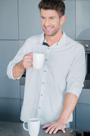 handome: Handsome man enjoying a mug of fresh coffee Stock Photo