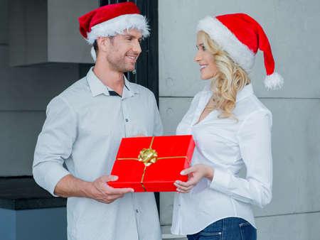 20 24: Pretty woman giving her husband a Christmas gift