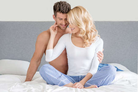 Sexy Young Couple on White Bed Fashion Shoot photo
