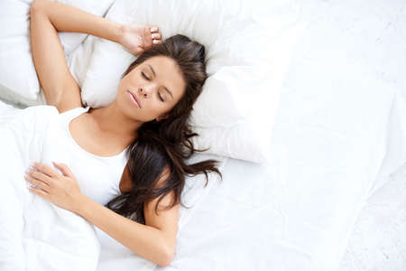 Pretty Young Woman Sleeping on White Bed Stock Photo