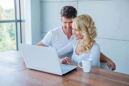 20 24: Couple smiling as they check their social media Stock Photo