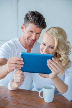 Couple smiling as they read a tablet computer photo