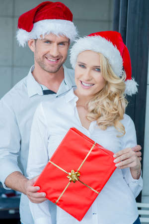 20 24: Smiling couple holding a red Christmas gift