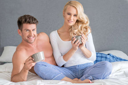 20 24: Middle Age White Couple Having Drink on Bed Stock Photo
