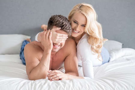 Smiling playful woman covering her husbands eyes photo