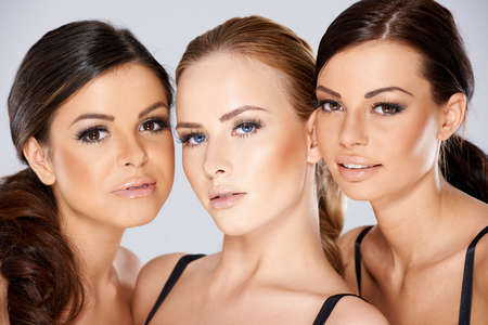 three: Close up Pretty Young Women Faces Stock Photo