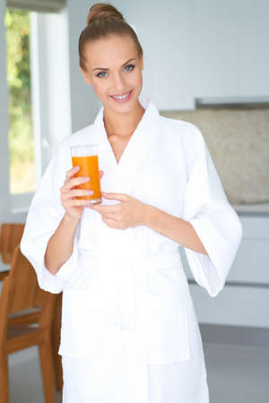 robes: Woman in bath robe drinking orange juice