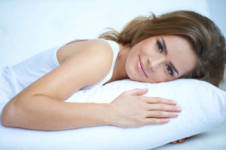 human stomach: Pretty Woman Lying Prone on White Pillow Stock Photo
