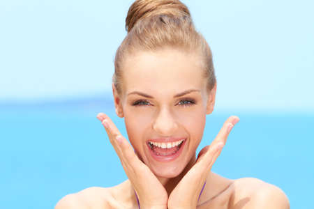 smile faces: Happy Blond Woman with Hands on Chin Stock Photo