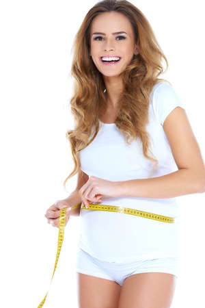 woman measuring: Pregnant Woman Measuring Waist with Tape Measure