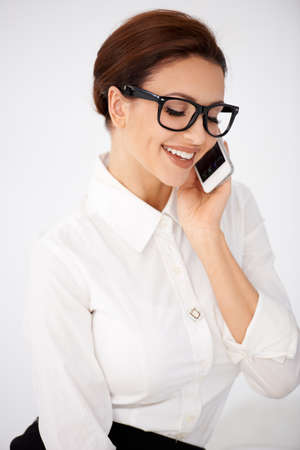 entrepeneur: Businesswoman in glasses chatting on a mobile Stock Photo