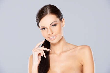 tetona: Bare Mujer pelo largo sobre fondo gris Foto de archivo