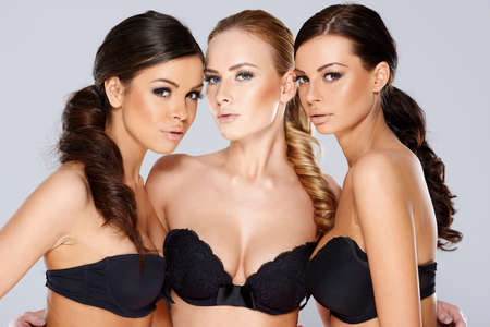 modelos posando: Cierre de Tres Preciosas Mujeres j�venes en Strapless Negro Sexy Bras mira la c�mara sensualmente. Aislado en el fondo gris. Foto de archivo