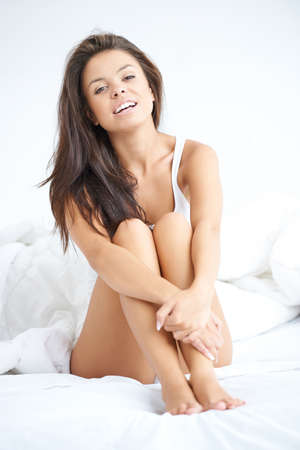 Young Woman in Night Wear Sitting on White Bed photo