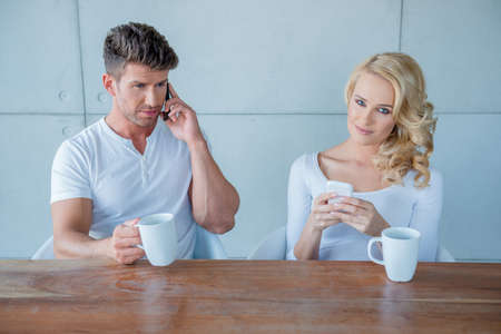 Sitting Couple Having Coffee with Mobile Phones photo