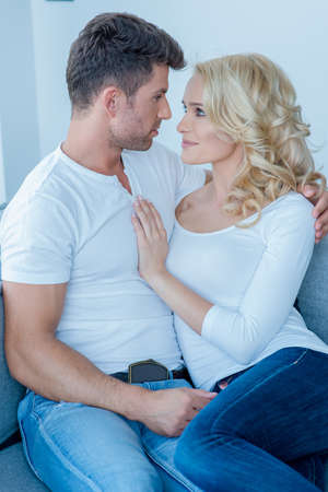 couple couch: Romantic Couple Sitting on the Couch Stock Photo