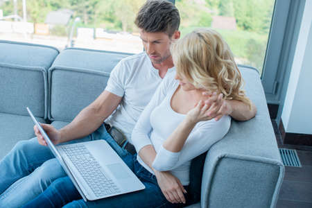 Sweet Couple on Sofa Watching Something at Laptop photo