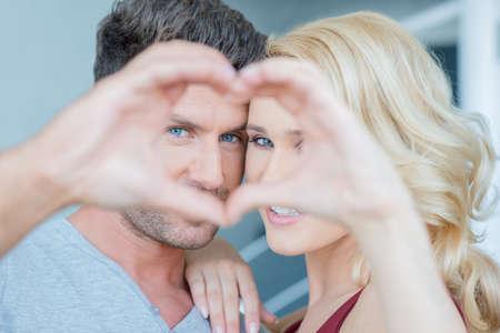 couple  amoureux: Couple Regarder � travers les mains Faire Coeur