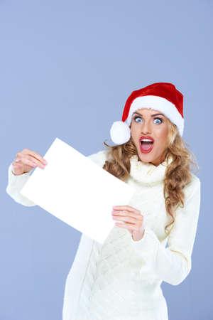 cara sorpresa: Mujer rubia que sostiene el papel en blanco en la cara de sorpresa