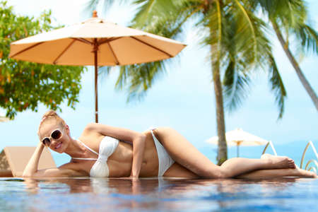 Blond woman sunbathing on an infinity pool photo