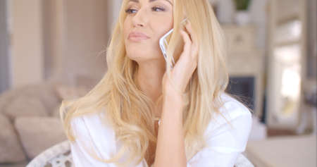 demure: Happy Blond Female Calling at Phone Looking Left Stock Photo