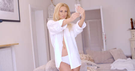 puckering lips: Sexy Blond Woman in White Taking Selfie Stock Photo