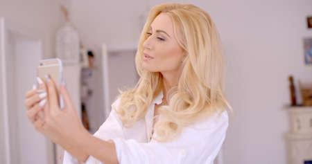 puckering lips: Gorgeous Blond Woman Taking Selfie Photo