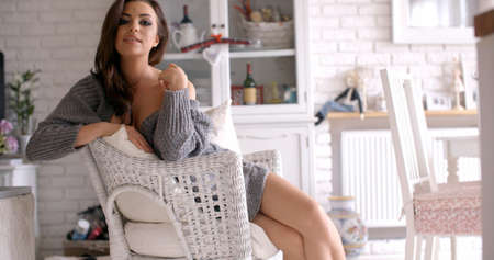 red cardigan: Seductive Woman Sitting on a White Chair Stock Photo